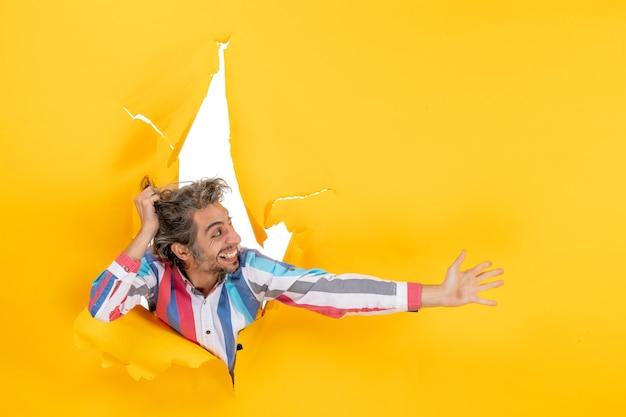 Vooraanzicht van een emotionele en uitgeputte jonge kerel gefocust op iets door een gescheurd gat in geel papier yellow