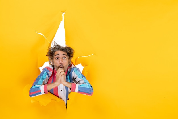 Vooraanzicht van een emotionele en uitgeputte jongeman door een gescheurd gat in geel papier