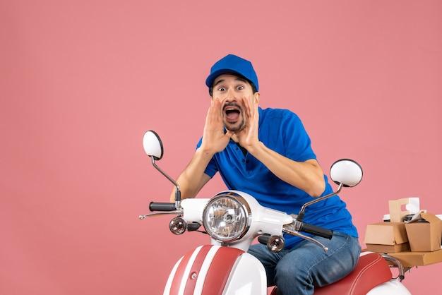 Vooraanzicht van een emotionele koeriersman met een hoed die op een scooter zit en iemand belt op een pastelkleurige perzikachtergrond
