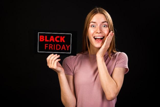 Vooraanzicht van een enthousiaste vrouw die een zwarte vrijdagkaart houdt