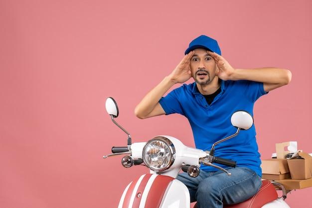 Vooraanzicht van een gefocuste koeriersman met een hoed die op een scooter zit op een pastelkleurige perzikachtergrond