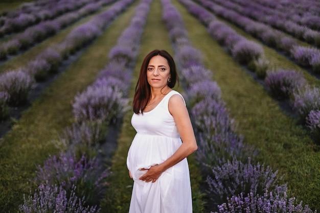 Vooraanzicht van een geglimlachte brunette blanke zwangere vrouw gekleed in witte jurk, buik aanraken in lavendelveld.
