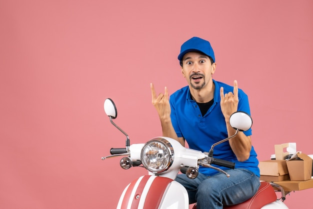 Vooraanzicht van een gekke emotionele koeriersman met een hoed die op een scooter zit op een pastelkleurige perzikachtergrond