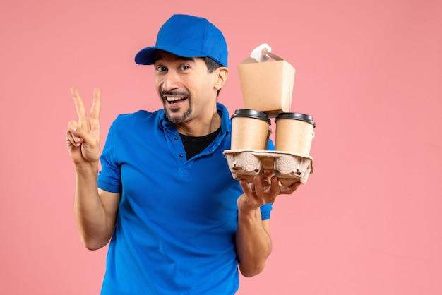 Vooraanzicht van een gekke emotionele mannelijke bezorger die een hoed draagt die bestellingen vasthoudt en een overwinningsgebaar maakt