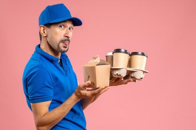Vooraanzicht van een gekke emotionele mannelijke bezorger met een hoed die bestellingen vasthoudt