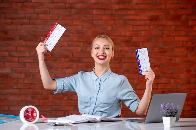 Vooraanzicht van een gelukkig reisbureau dat achter haar werkplek zit en kaartjes vasthoudt global manager agentschap kaart binnenshuis bezetting assistent dienst vlucht toerisme