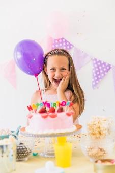 Vooraanzicht van een gelukkige ballon die van de meisjesholding van verjaardagsviering geniet