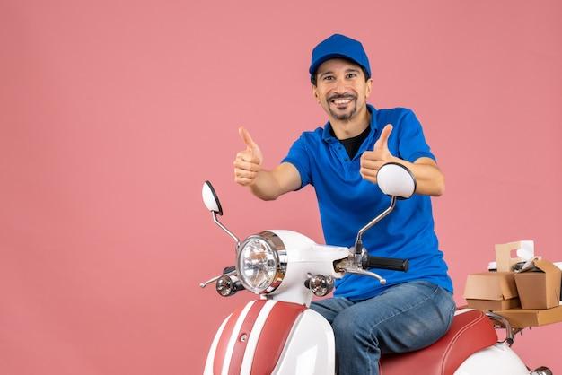 Vooraanzicht van een gelukkige bezorger met een hoed die op een scooter zit en een goed gebaar maakt op een pastelkleurige perzikachtergrond