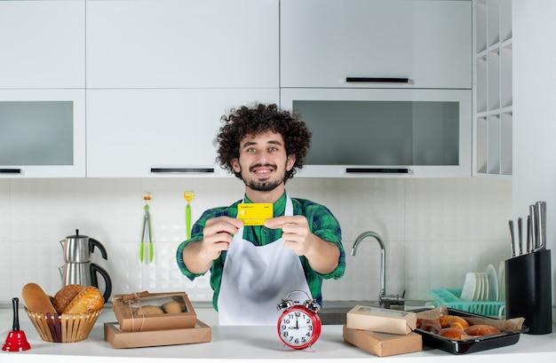 Vooraanzicht van een gelukkige jonge man die achter de tafel staat met verschillende gebakjes erop en een bankkaart in de witte keuken laat zien