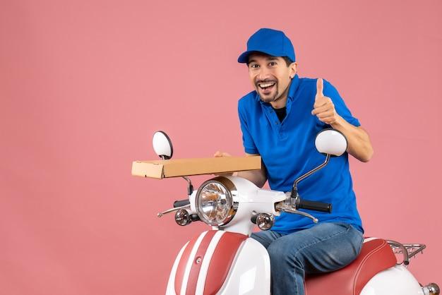 Vooraanzicht van een gelukkige koeriersman met een hoed die op een scooter zit en een bestelling houdt die een goed gebaar maakt op een pastelkleurige perzikachtergrond