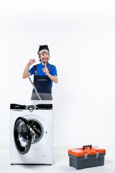 Vooraanzicht van een gelukkige reparateur in uniform staande achter de wasmachine met pijp op een witte muur