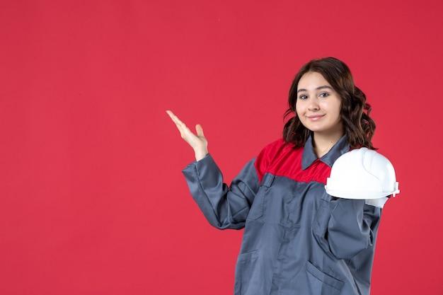 Vooraanzicht van een gelukkige vrouwelijke architect die een helm vasthoudt en aan de rechterkant op een geïsoleerde rode achtergrond wijst