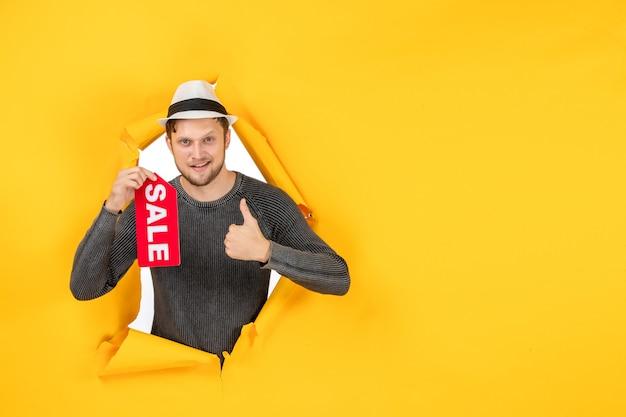 Vooraanzicht van een geschokte jonge volwassene die een verkoopteken toont en een goed gebaar maakt in een gescheurde gele muur