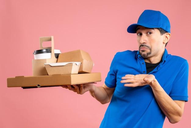 Vooraanzicht van een geschokte, verraste mannelijke bezorger met een hoed die bestellingen toont