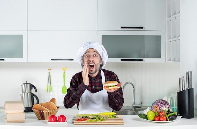 Vooraanzicht van een geschreeuwde man die een hamburger omhoog houdt die achter de keukentafel staat