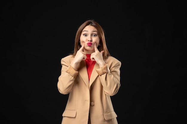 Vooraanzicht van een gespannen en emotionele jonge dame in een lichtbruin pak op dark
