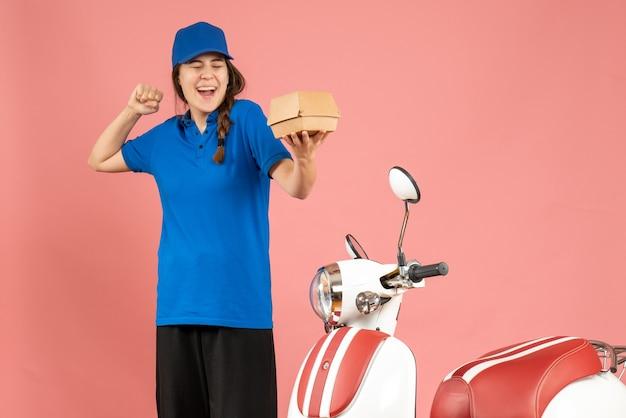 Vooraanzicht van een glimlachend koeriersmeisje dat naast een motorfiets staat met cake op een pastelkleurige perzikkleurige achtergrond