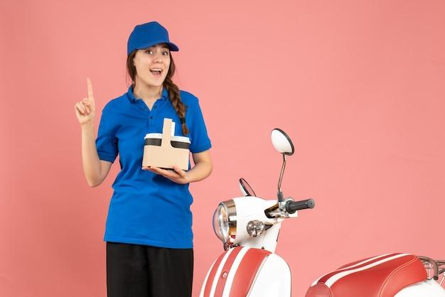 Vooraanzicht van een glimlachend koeriersmeisje dat naast een motorfiets staat met koffie die omhoog wijst op een pastelkleurige perzikkleurige achtergrond