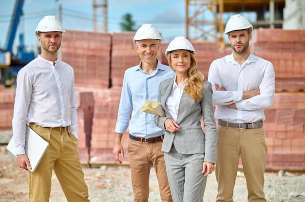 Vooraanzicht van een glimlachende aantrekkelijke vrouwelijke bouwmanager met een tekening en knappe bouwers in veiligheidshelmen die vooruitkijken