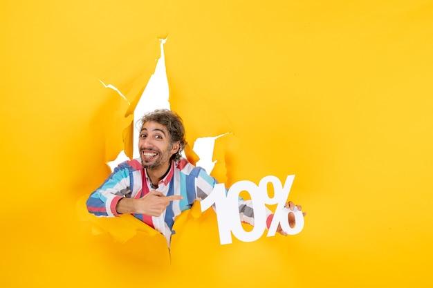 Vooraanzicht van een glimlachende en zelfverzekerde jongeman die tien procent wijst in een gescheurd gat in geel papier