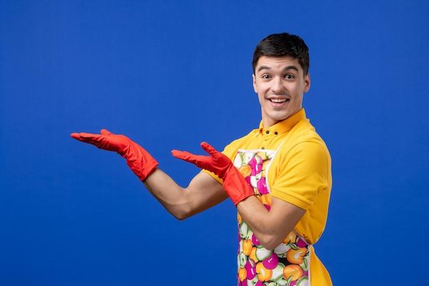 Vooraanzicht van een glimlachende huishoudster die zijn handen uitstrekt en op een blauwe muur staat
