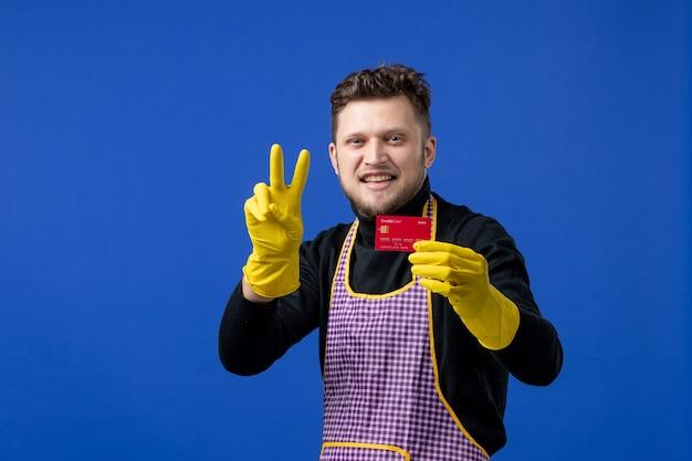 Vooraanzicht van een glimlachende jonge man die een overwinningsteken op een blauwe muur maakt