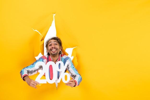 Vooraanzicht van een glimlachende jonge man die twintig procent toont in een gescheurd gat in geel papier