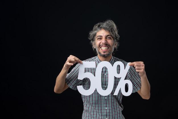 Vooraanzicht van een glimlachende man die een teken op een donkere muur vasthoudt