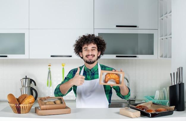 Vooraanzicht van een glimlachende man die versgebakken gebak in een kleine doos houdt en een goed gebaar maakt in de witte keuken