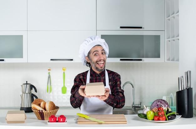 Vooraanzicht van een glimlachende mannelijke chef-kok die een doos vasthoudt die achter de keukentafel in de keuken staat