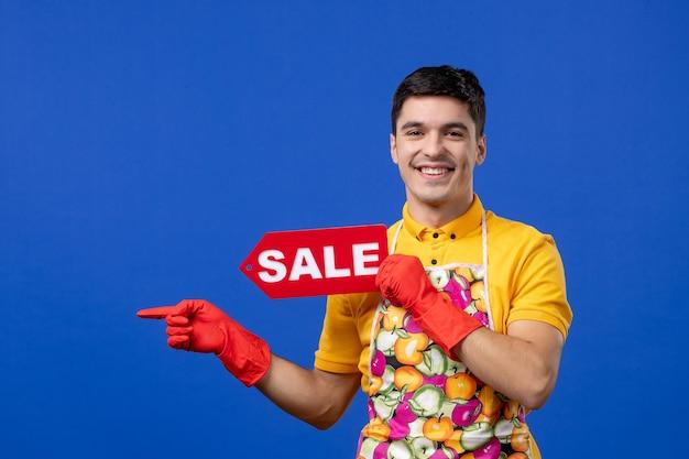 Vooraanzicht van een glimlachende mannelijke huishoudster in een geel t-shirt met een verkoopbord dat naar links op de blauwe muur wijst