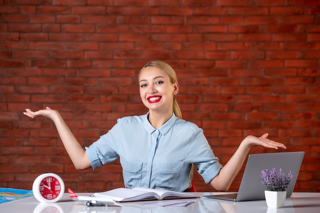 Vooraanzicht van een glimlachende reisagent die achter haar werkplek zit toeristische dienstkaart global agency assistent manager binnenshuis bezetting