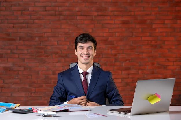 Vooraanzicht van een glimlachende reisagent die achter zijn werkplek zit in pak zakelijk toerisme bezetting servicebureau assistent project global