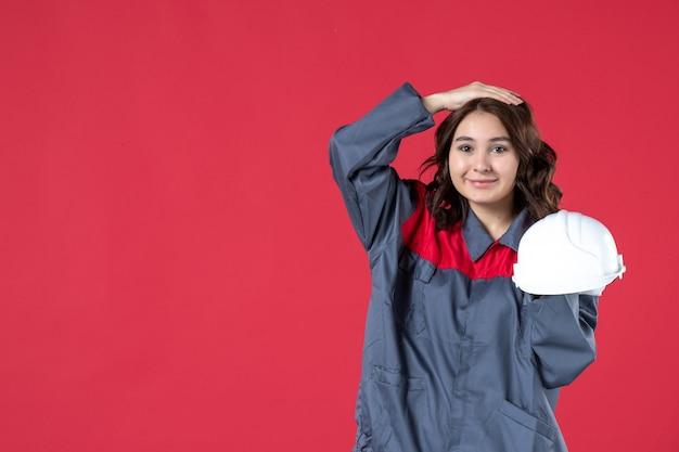 Vooraanzicht van een glimlachende vrouwelijke architect die een harde hoed vasthoudt en de hand op haar hoofd legt op een geïsoleerde rode achtergrond