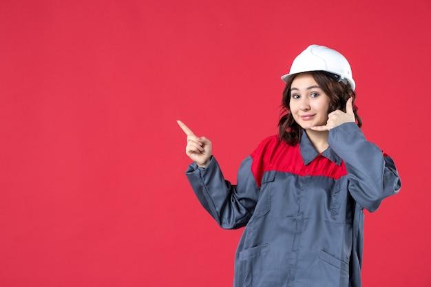 Vooraanzicht van een glimlachende vrouwelijke bouwer in uniform met harde hoed en het maken van een gebaar dat omhoog wijst op een geïsoleerde rode achtergrond