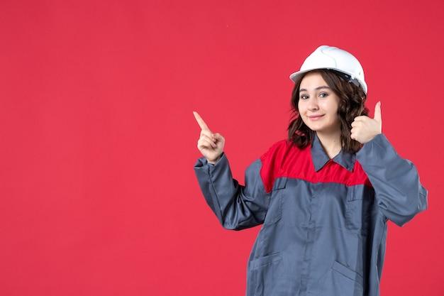 Vooraanzicht van een glimlachende zelfverzekerde vrouwelijke bouwer in uniform met harde hoed en een goed gebaar makend naar boven op geïsoleerde rode achtergrond