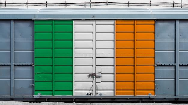 Vooraanzicht van een goederenwagon van de containertrein met een groot metaalslot met de nationale vlag van ierland. het concept van export en import, transport, nationale levering van goederen
