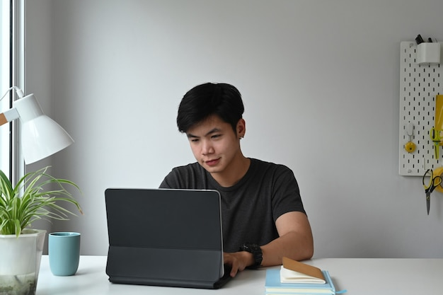 Vooraanzicht van een grafisch ontwerper werkt aan een computertablet op zijn creatieve werkruimte.