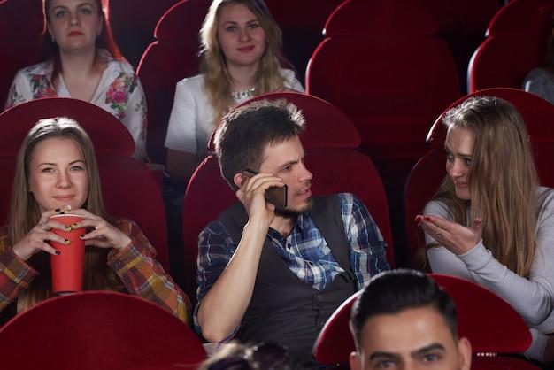 Vooraanzicht van een groep mensen kijken naar film in de bioscoopzaal, donkerbruine man praten op oproep telefoon, boos en geschokt vrouw gebaren met de hand hem te stoppen. vrije tijd en cultuur van jonge meisjes en jongens.