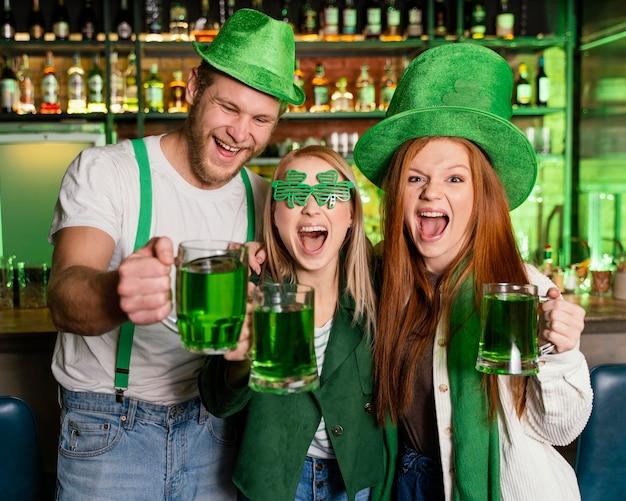 Vooraanzicht van een groep vrienden die st. patrick's day aan de bar