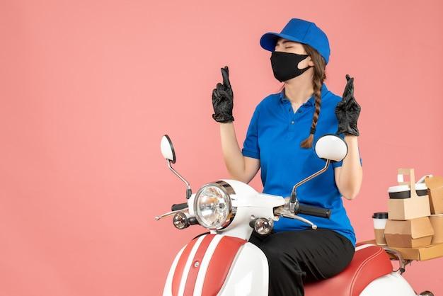 Vooraanzicht van een hoopvol koeriersmeisje met een medisch masker en handschoenen die op een scooter zitten en bestellingen afleveren op een pastelkleurige perzikachtergrond