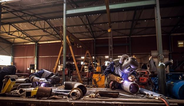 Vooraanzicht van een industriële werkruimte met mensen in beschermende uniforme snijden van metalen buizen.