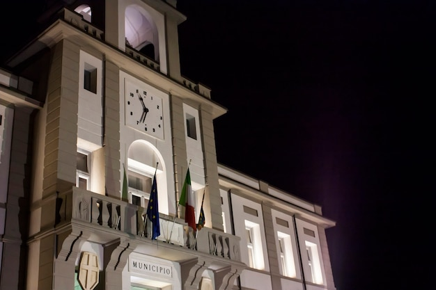 Vooraanzicht van een italiaans stadhuis (porto viro) in veneto, 's avonds hervat met verlichte lichten.