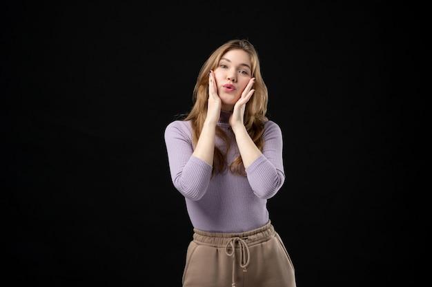 Vooraanzicht van een jong blond meisje dat haar handen op de wangen op het donker legt