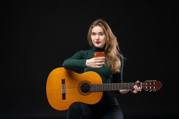 Vooraanzicht van een jong, mooi musicusmeisje dat gitaar vasthoudt en een bankkaart aanwijst die voor de camera op dark