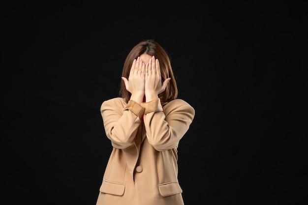 Vooraanzicht van een jonge dame in een lichtbruin pak dat haar gezicht bedekt met de handen op het donker