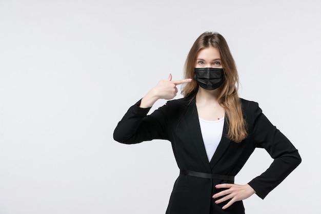 Vooraanzicht van een jonge dame in pak die een chirurgisch masker draagt en iets aan de linkerkant op wit wijst