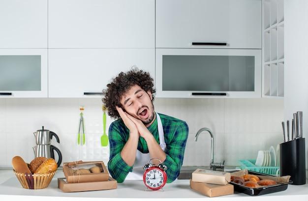 Vooraanzicht van een jonge dromerige man die achter de tafelklok staat, verschillende gebakjes erop in de witte keuken