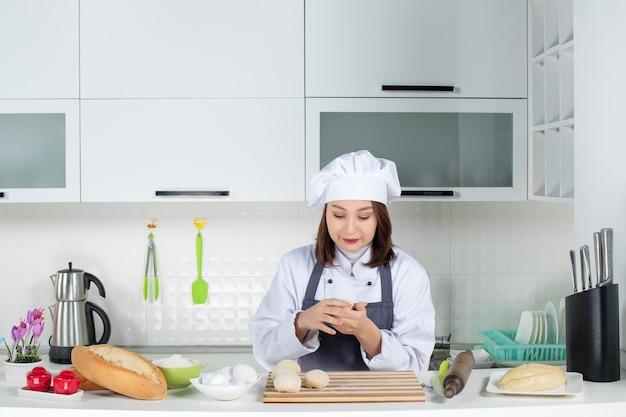 Vooraanzicht van een jonge drukke vrouwelijke chef-kok in uniform die achter de tafel staat en gebak bereidt in de witte keuken