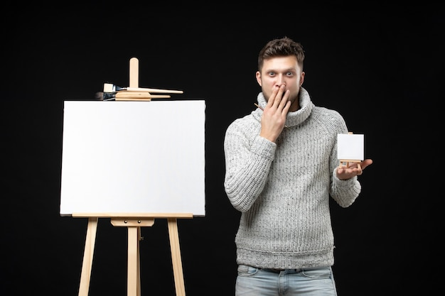 Vooraanzicht van een jonge en getalenteerde mannelijke artiest die een mini-penseelboek vasthoudt met een verbaasde gezichtsuitdrukking op zwart